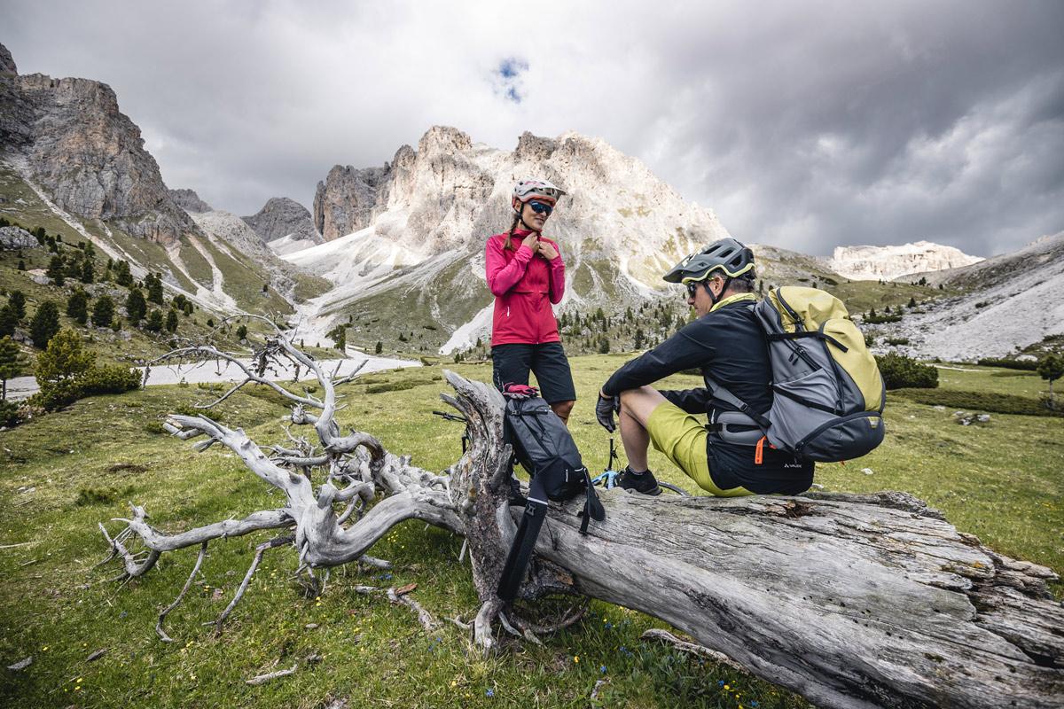 Frau und Mann in den Bergen machen Rast während einer Mountainbike Tour.