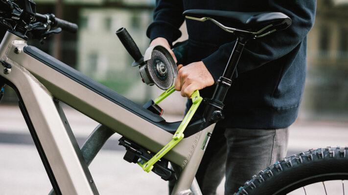 Dieb bricht das Faltschloss eines E-Bikes mit einer Akku-Flex auf.
