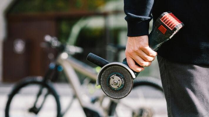 Dieb hält eine Akku-Flex in der linken Hand, im Hintergrund steht ein E-Bike.