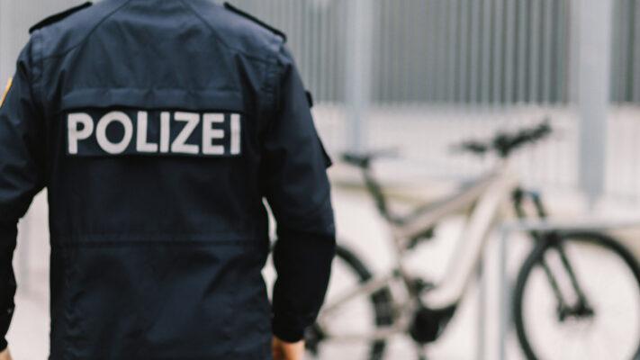 Polizist in Uniform nähert sich einem E-Bike.