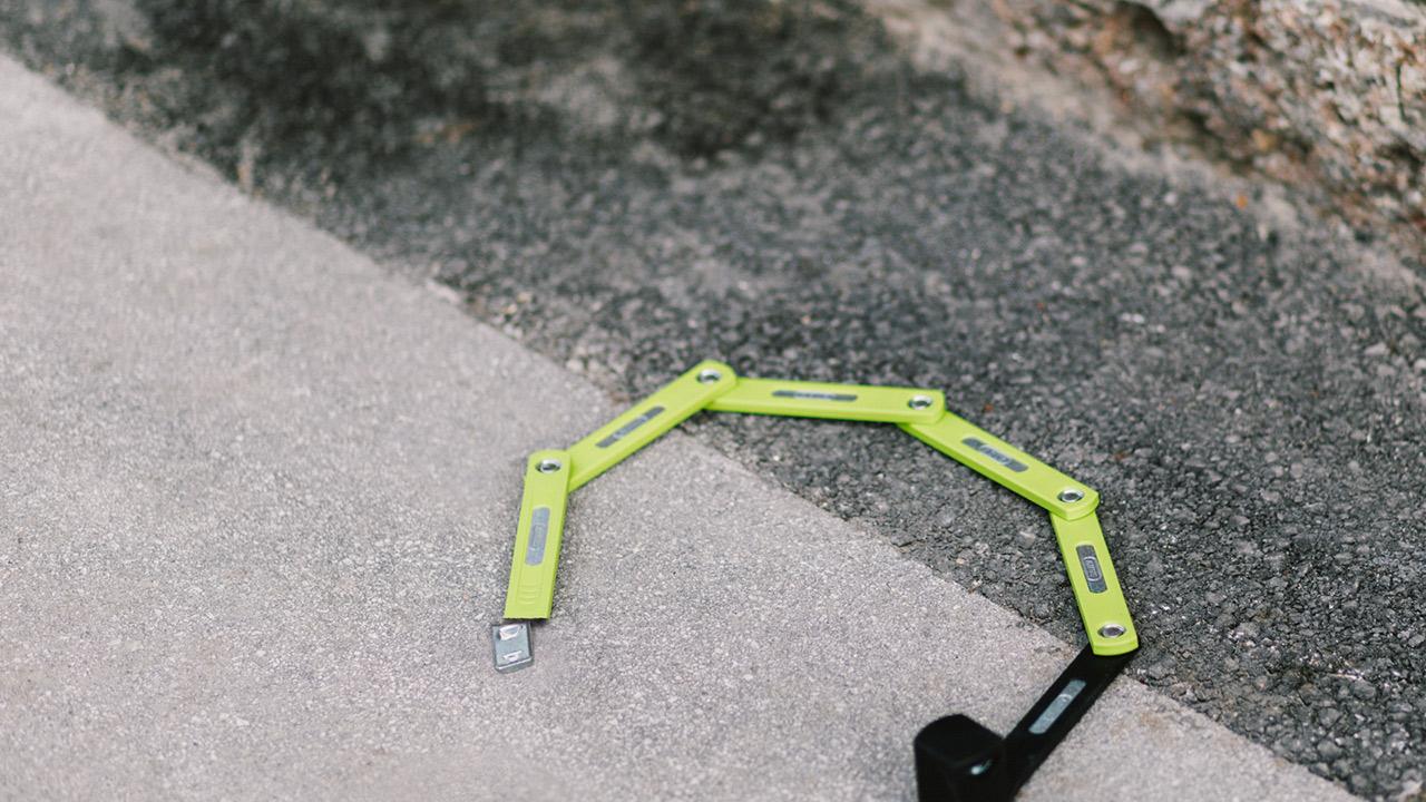 A broken bicycle folding lock lies broken open on the asphalt floor.